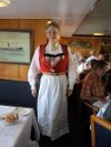 Deirdre in her bunad ([19th-century invented] traditional formal peasant dress in Hardangerfjord, Norway), in July 2014 on MS Lofoten, one of a system of ferries running up and down the coast north of Bergen